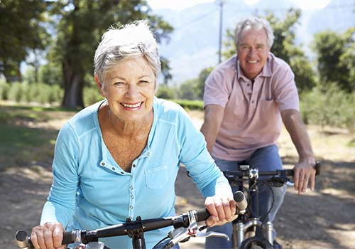 elderly couple smiling and riding bikes together