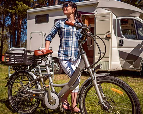 woman standing next to an electric bike outside of a small RV